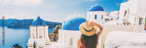 Summer travel tourist visiting Oia, Santorini, Europe vacation destination. Luxury holiday woman walking in city. Banner panorama.