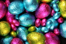 Pile Of Foil Wrapped Chocolate Easter Eggs In Pink, Blue & Lime Green.