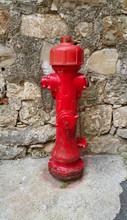 Red Fireplug Against A Stone W...
