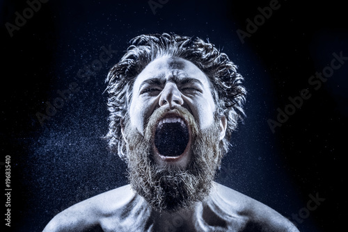 Cuadros en Lienzo A bearded man angrily screams into a spray of water against a black background