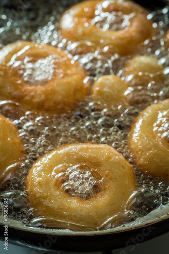 Frying homemade sweet donuts on hot oil
