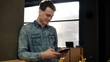 Young attractive sexy guy in denim shirt standing and scrolling something on his smartphone. Indoors footage. Concentration.