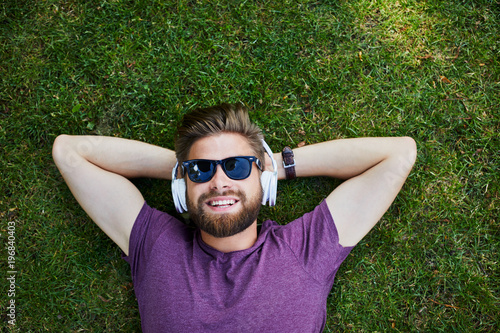 Poster Magasin de musique Happy man listening to music while lying on the grass outdoors and wearing sunglasses