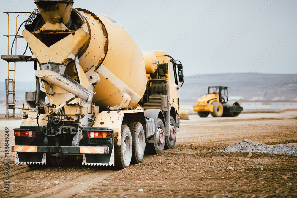 Fototapety, obrazy: Industrial Cement truck on highway construction site. Heavy duty machinery at work on construction site