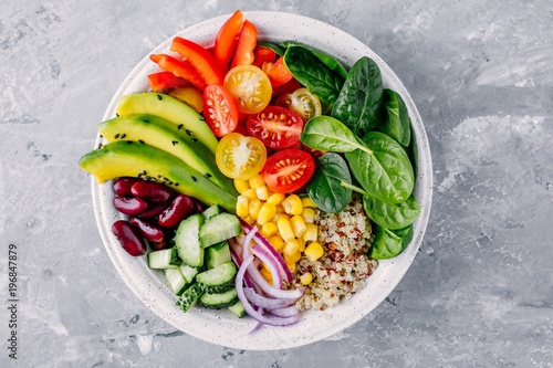 Healthy vegan lunch Buddha bowl. Avocado, quinoa, tomato, cucumber, red beans, spinach, red onion and red paprika vegetables salad.
