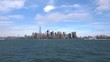 A long shot of downtown New York and boats passing the cityscape