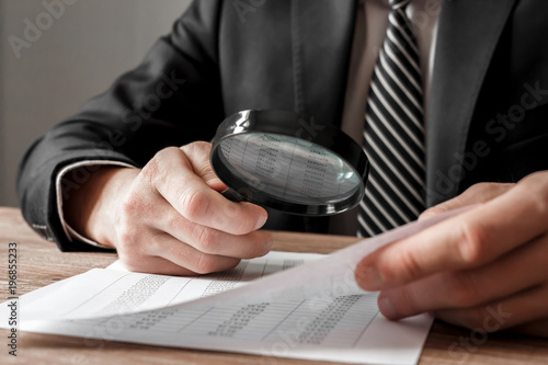 Fotografie, Obraz  Businessman holding magnifying glass zoom and analyzing financial indicators