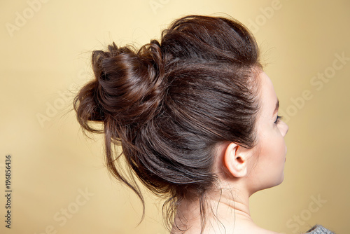 Fototapeta Rear view of female hairstyle middle bun with brown hair. obraz