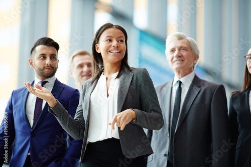 Photo  Young businesswoman or guide showing group of delegates interior of new building