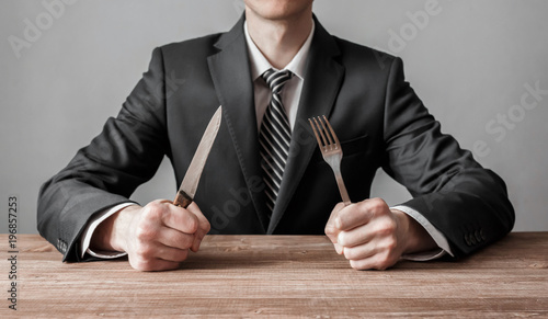 Cuadros en Lienzo Businessman holding fork with knife and ready to eat