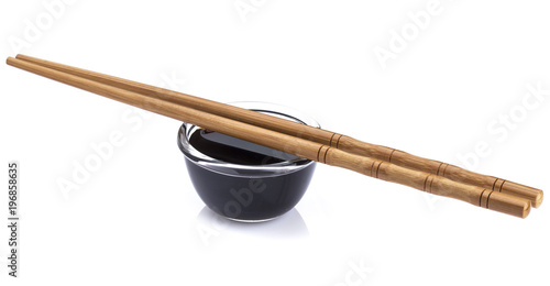 Soy sauce and bamboo chopsticks on white background