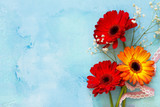 A wedding story or background Mother's Day. Three gerbera flowers  on a stone background or slate with copy space. Copy space, top view flat lay background.