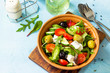 Greek salad with fresh vegetables, feta cheese and black olives on a blue stone or concrete table. Diet, concept of vegetarian food. Copy space.