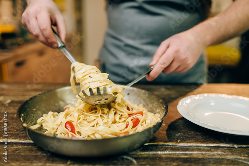 Foto op Plexiglas Koken Chef cooking pasta, pan on wooden kitchen table