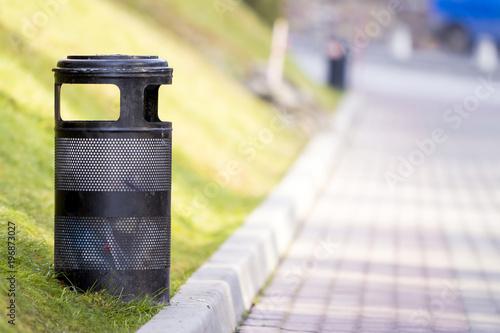 Black metal garbage bin in park with blurred sunny background Wallpaper Mural