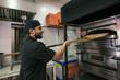 Arab turkish man preparing pizza in owen at his little business store