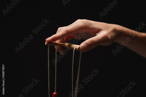 Manipulators hand with marionette string isolated on black Canvas Print