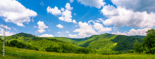 Foto op Plexiglas Landschappen panorama of beautiful countryside in summer. beautiful landscape with forested mountains and grassy field under the blue sky with some clouds