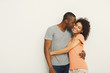 Smiling black couple embracing at white studio