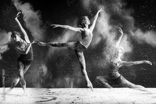 Fotografie, Tablou  beautiful ballet dancer dancing barefoot on black background in a cloud of dust
