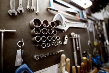 Uchwyt na narzędzia warsztatowe z kluczem i zestawem kluczy nasadowych.