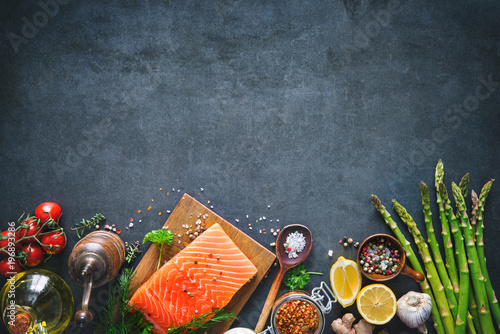 Photo  Fresh salmon fillet with aromatic herbs, spices and vegetables