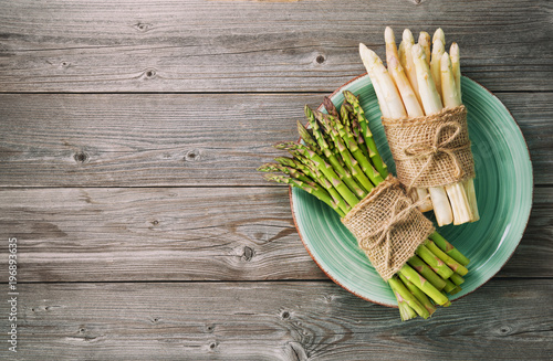 Fotografía  Bunches of fresh green and white asparagus on wooden background