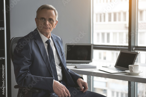 Fotografie, Obraz  Portrait of calm mature male locating at desk with appliance during job in room