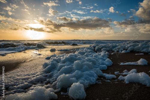 Plakat Morze piana na plaży o zachodzie słońca