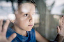 One Sad Little Boy Standing Near The Window At The Day Time.