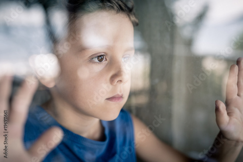 one sad little boy standing near the window at the day time. Wallpaper Mural