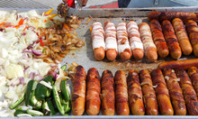 Street Vendor Cooking Bacon Wrapped Hot Dogs With Onions And Jalapeno Peppers. Popular Cuisine For Street Fairs And Events