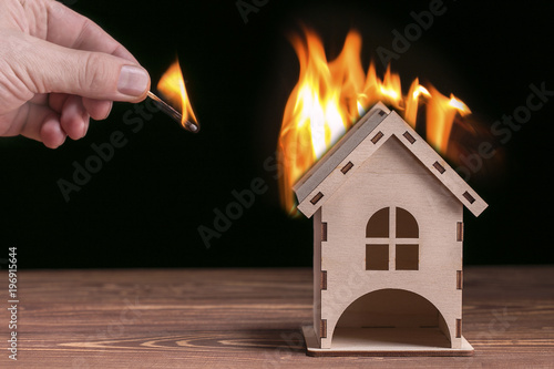 Fotografía  Model house in fire and hand with matchstick on a black background