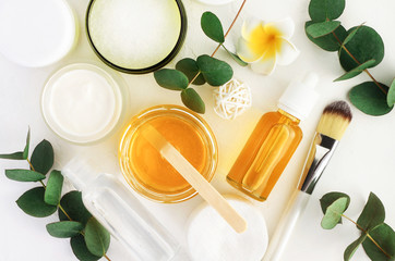 FototapetaNatural cosmetics ingredients for skincare, body and hair care. Golden honey in jar and green herbal eucalyptus leaves. Top view bottles with facial treatment product white background.