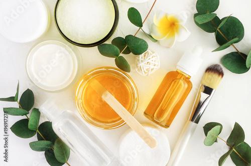 Naturalne składniki kosmetyków do pielęgnacji skóry, ciała i włosów. Złoty miód w słoiku i zielone ziołowe liście eukaliptusa. Odgórnego widoku butelki z twarzowym traktowanie produktu bielu tłem.