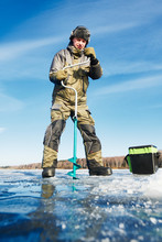 Fisherman With Auger In Winter...