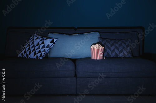 Comfortable couch with popcorn indoors. Home cinema - 196924218