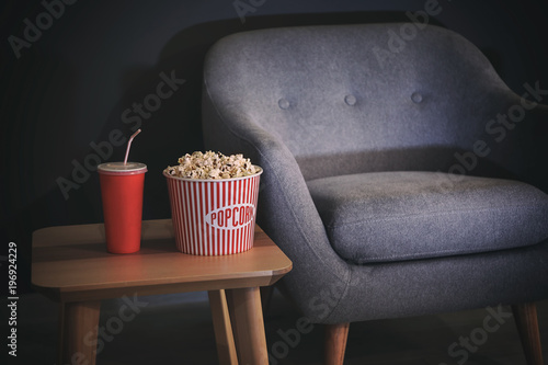 Table with popcorn and drink near comfortable armchair indoors. Home cinema