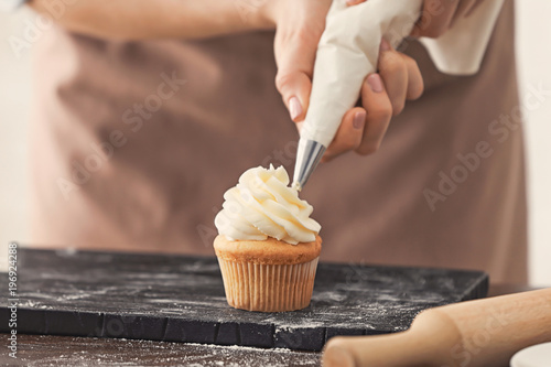 Woman decorating tasty cupcake with cream at table Wallpaper Mural