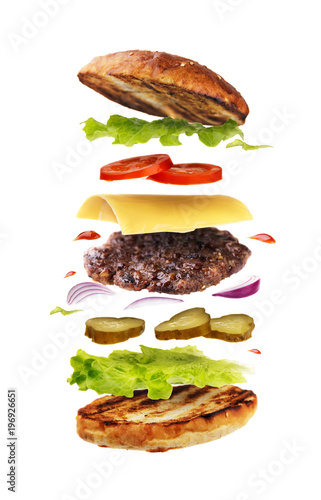 Delicious hamburger with flying ingredients isolated on white background. Freshly brewed burger closeup