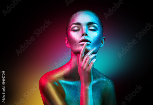 Poster Beauty Fashion model woman in colorful bright sparkles and neon lights posing in studio, portrait of beautiful sexy girl. Art design colorful vivid makeup