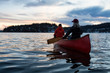 canvas print picture - Couple friends on a wooden canoe are paddling in an inlet surrounded by Canadian mountains during a vibrant sunset. Taken in Indian Arm, near Deep Cove, North Vancouver, British Columbia, Canada.