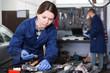 Woman employee is choosing instruments for repair car