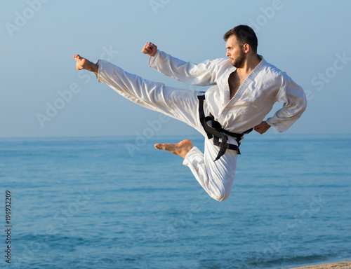 Garden Poster Martial arts young man practicing karate positions