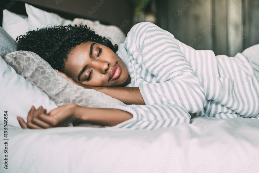 Fototapeta close up of a pretty black woman with curly hair sleeping in bed closed eyes