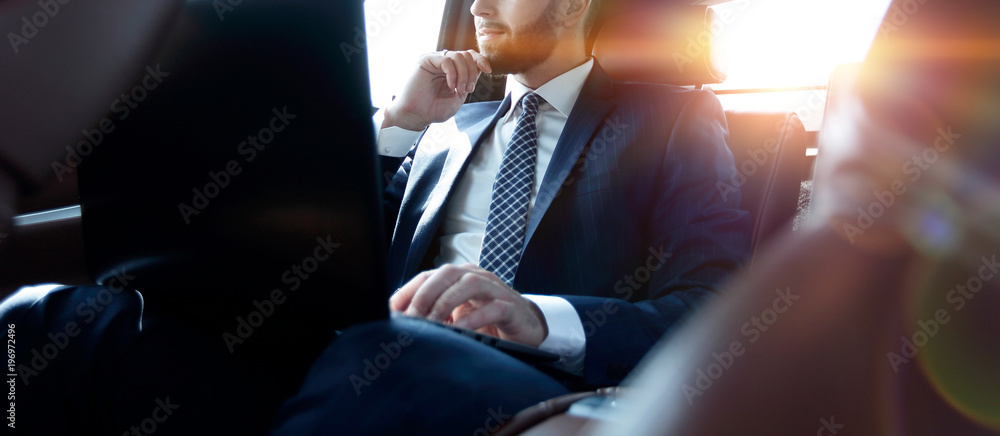 Fototapeta businessman working with laptop and looking out the window of a