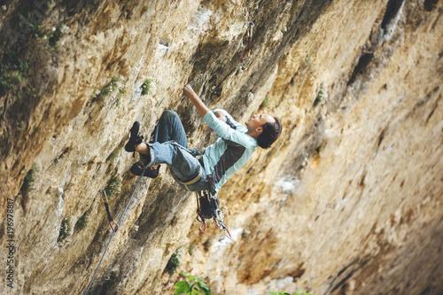Poster Rock climber climbing orange limestone wall reaching across for handhold on rock