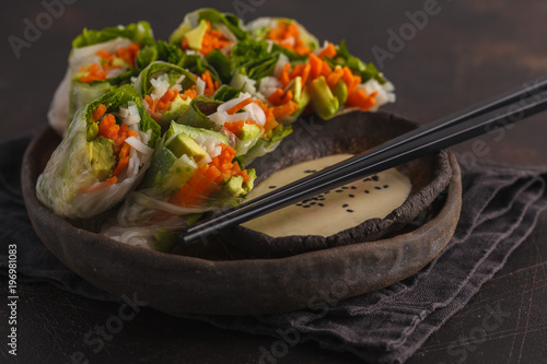 Fresh handmade vegan asian spring rolls with rice noodles, avocado, carrots and tahini dressing on black dish, dark background.