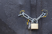 Padlock With Chain On The Iron Gate. Black Background. The Concept Protects Reliably.