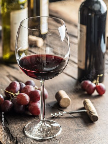 Glass of red wine on the table. Wine bottle and grapes at the background.